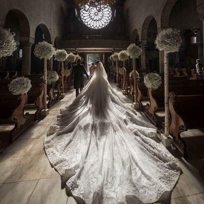 The bride wore a custom-made Michael Cinco gown costing over $1 million, embellished with 500,000 Swarovski crystals (because of course) and a whopping eight metre long veil and train.   Image: [@idoweddingsng](https://www.instagram.com/p/BVkpACiFLyU/)