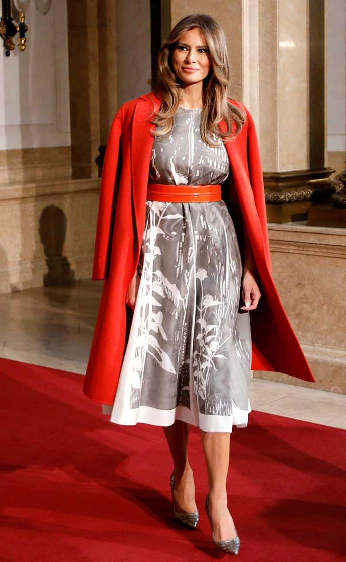 Melania continues to deliver at the G20 Summit, this time stepping out in a silk Jil Sander dress, complete with a cherry red Bottega Veneta coat and Manolo Blahnik pumps.