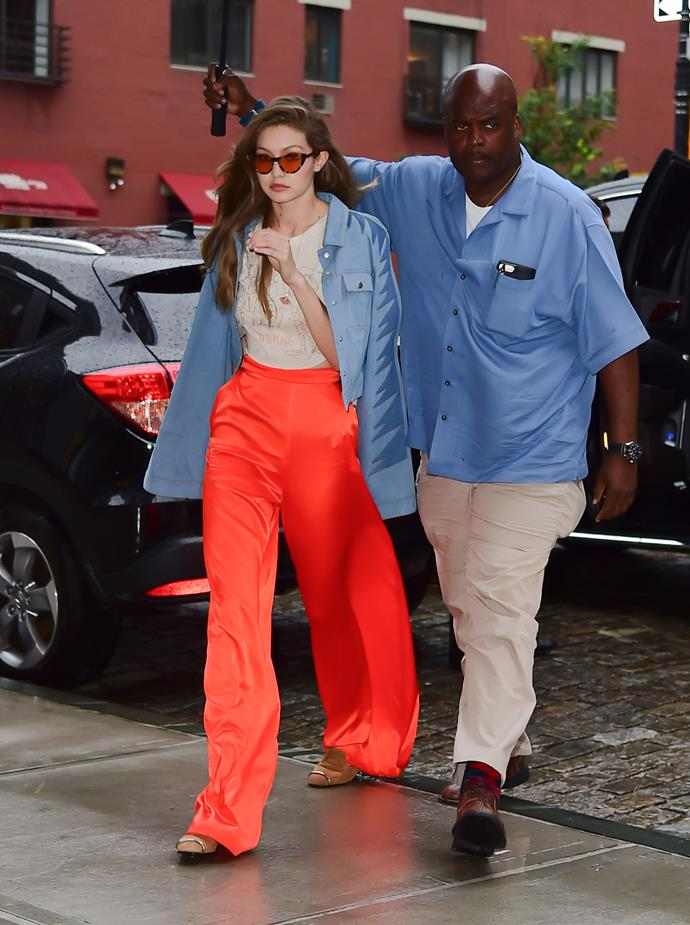 Gigi went colour-mad to offset a rainy NYC day, with bright-orange Stella McCartney pants and tinted retro shades.