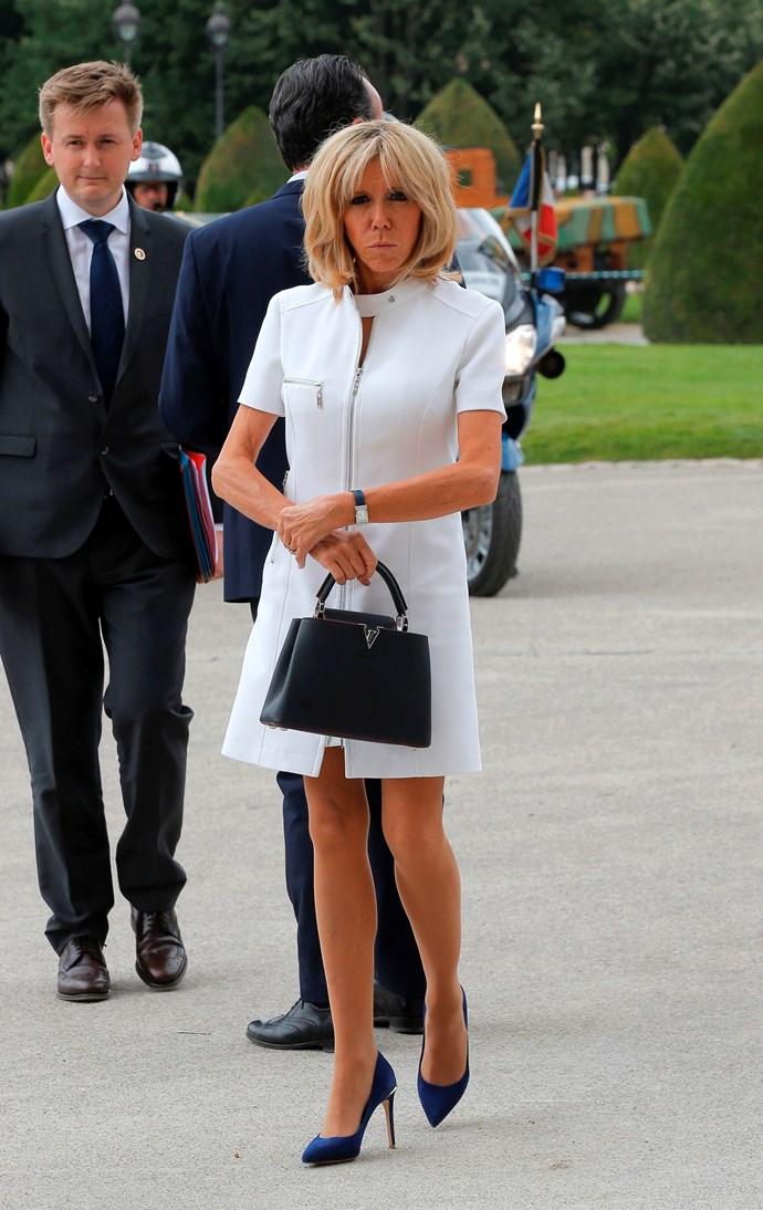 Brigitte Macron wears a Louis Vuitton dress and bag.