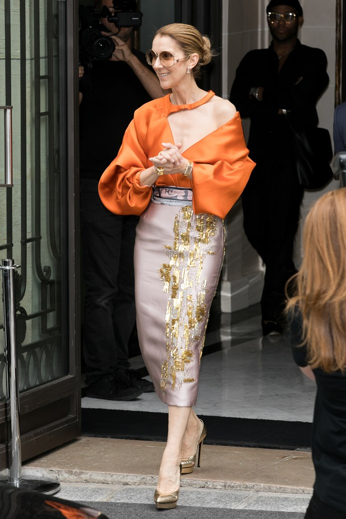 Céline left her hotel an orange off-the-shoulder number and sequined pencil skirt in Paris.