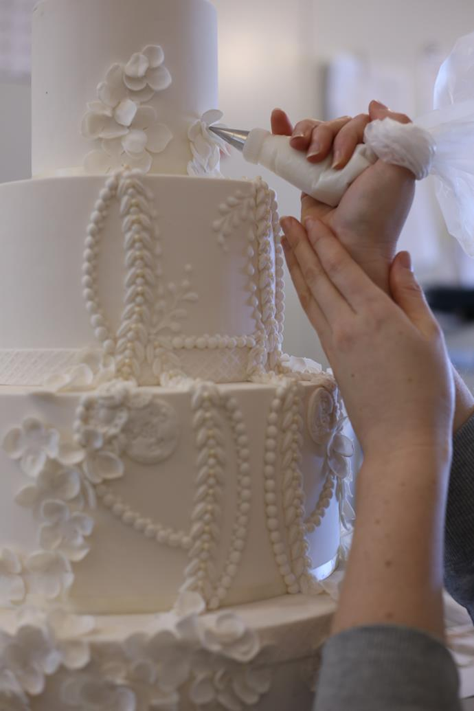 "**Step 9:** ""The finishing touches are added onto the cake, paying attention to fine detail. We always like to look at the cake in different positions to see if the cake looks right from all areas in the room."""