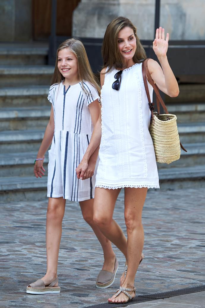 Queen Letizia demonstrated how a Queen does holiday style in Soller, Mallorca, for the Spanish royal family's summer vacation. The mother-of-two wore a thigh-skimming white lace dress, simple sandals and a very on-trend straw bag.