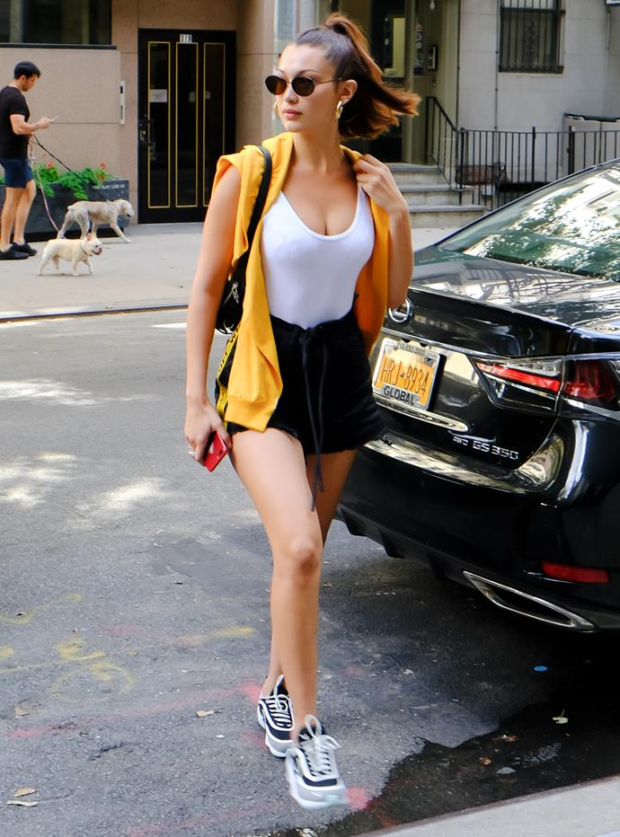 Bella stepped out in New York City wearing a white tank top, black loose-fit gym shorts and a canary yellow hoodie draped over her shoulders.