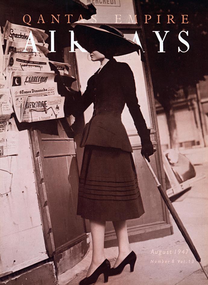 Christian Dior, Paris (fashion house); Christian Dior (designer) Model wears Black wool suit, spring−summer 1947 in Qantas Empire Airways magazine, August 1947. Qantas Heritage Collection, Sydney. Photo © Qantas Heritage Collection.