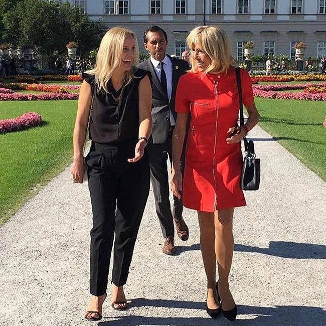 Brigitte Macron walks through the Mirabell Gardens in Salzburg, Austria, wearing a modern red dress with zipper details.