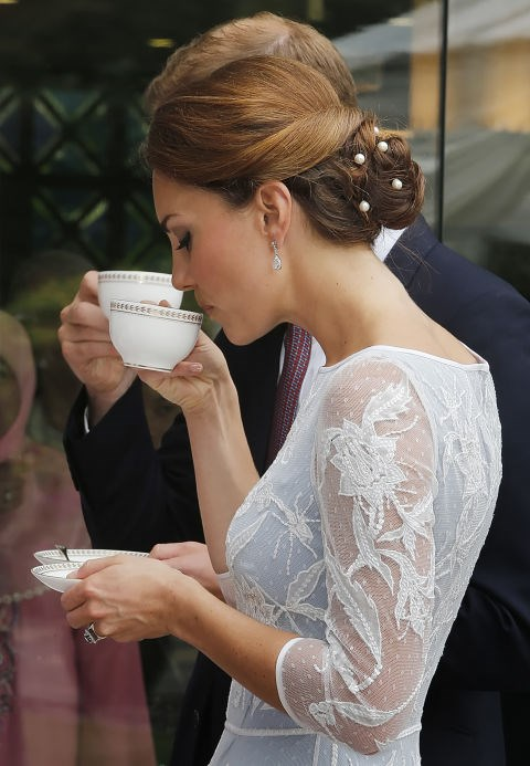 **...AS IS TEACUP HOLDING.** <br><br> Royal Family members pinch the teacup handle with their index finger and thumb, while their middle finger secures the bottom.