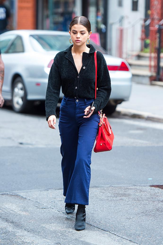 **September 3rd, 2017**  Accessorising again with her red Coach bag, Selena paired flared-leg trousers with black Stuart Weitzman boots and big gold hoops while out in New York.