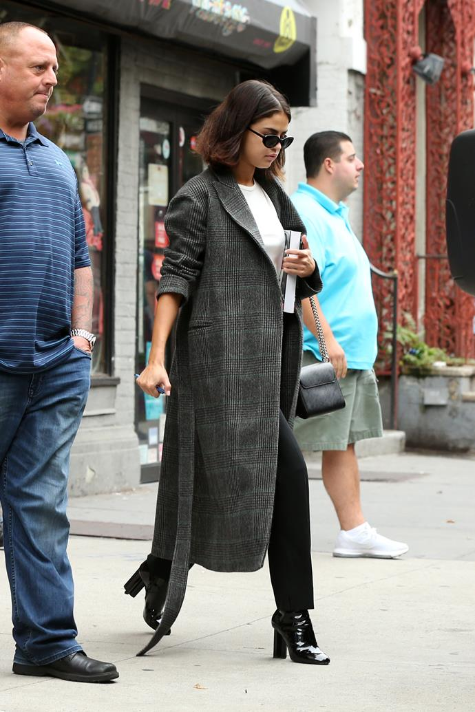 **September 2017**  Selena accessorised a trench coat with black patent leather boots and her signature '90s shades, as well as a Louis Vuitton Twist handbag, in New York. *(Image: Splash)*