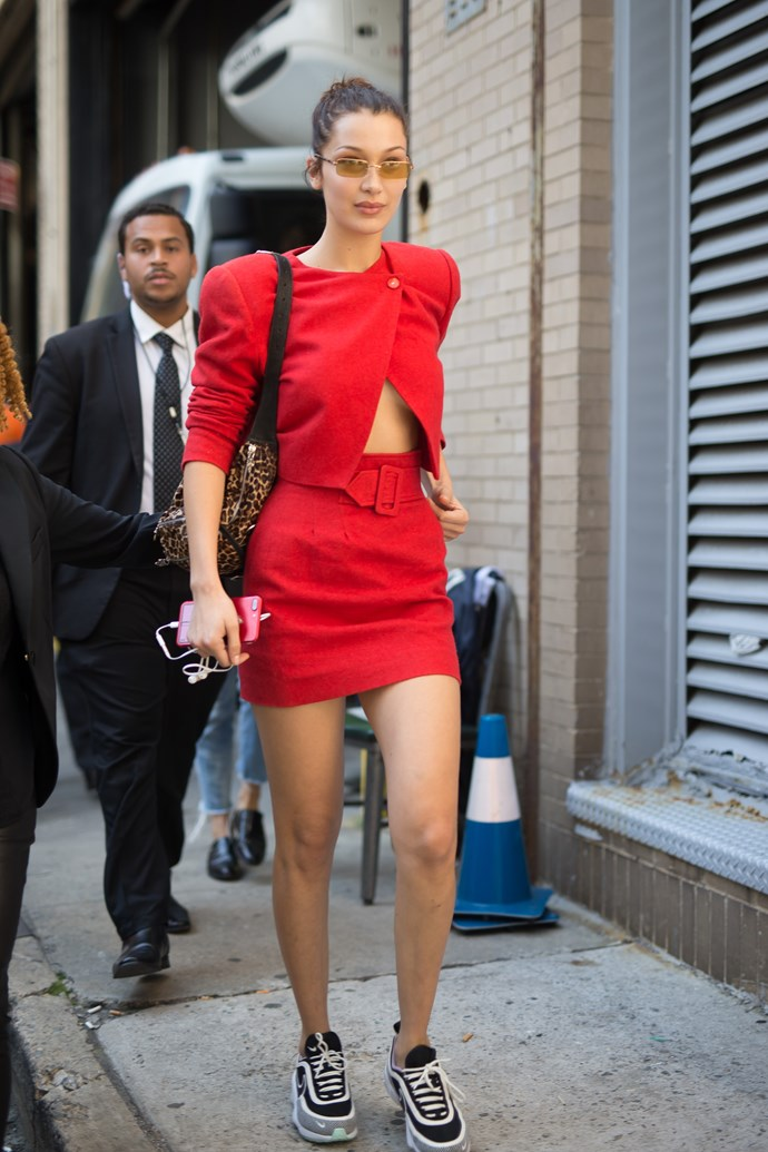 Bella steps out in a red two piece suit, with a classic '80s style belt and sneakers during New York Fashion Week.
