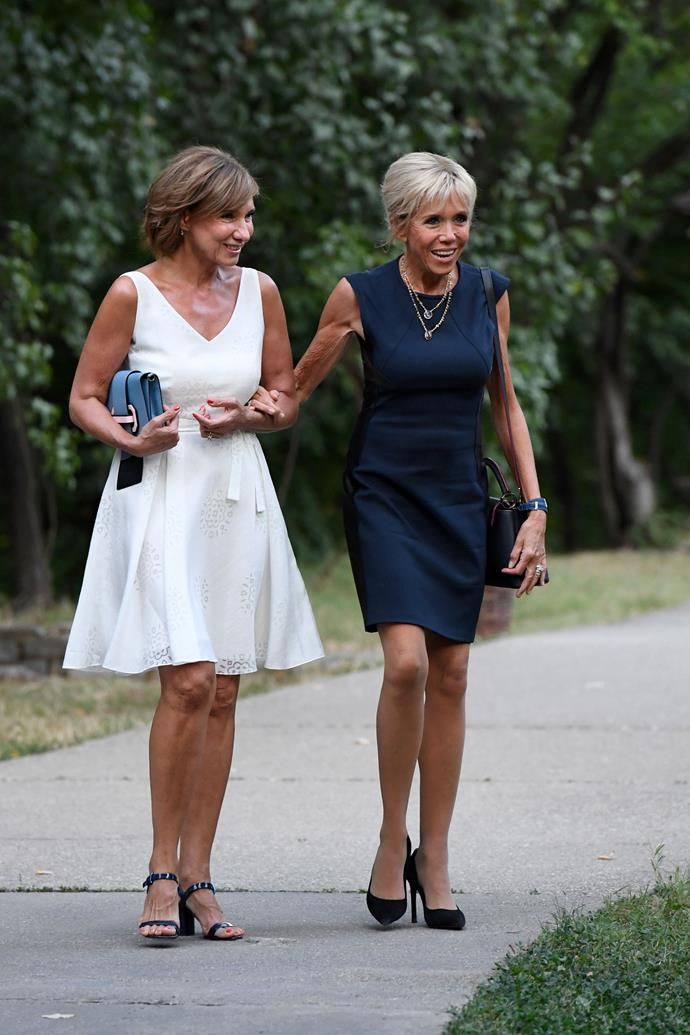 In her signature navy mini dress, with the first Lady of Romania, Carmen Iohannis.