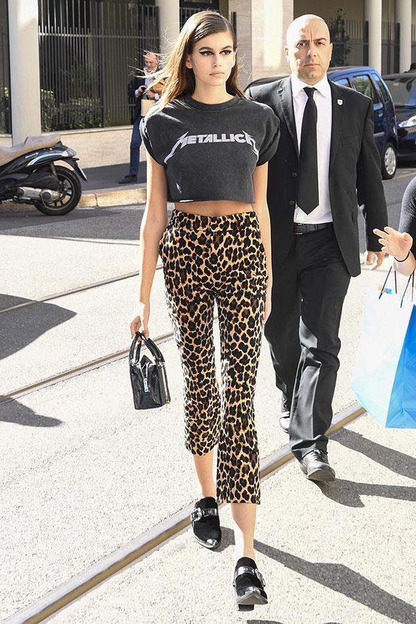Kaia stepped out at Milan fashion week wearing the classic cool girl uniform: a distressed band tee, bold leopard print and fierce eyeliner. <br><br> Image: Splash