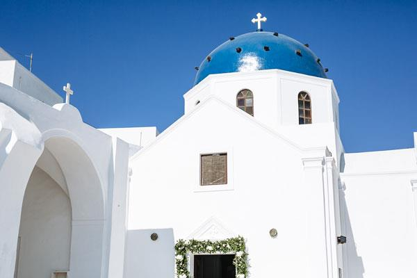 **On their ceremony and reception:** The ceremony was at a beautiful orthodox church called Anastasi in Imerovigli, Santorini overlooking the iconic caldera. The reception was at Rocabella, a short drive away from the church.