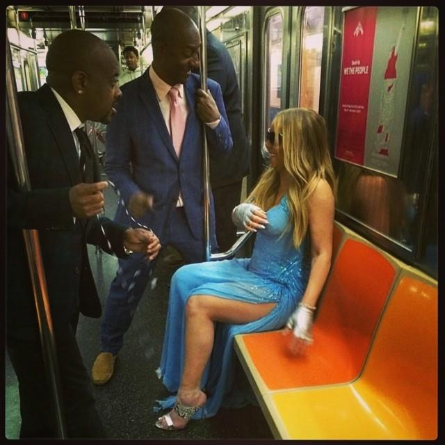 Mariah Carey riding the subway in a blue bejewelled gown and silver heels.