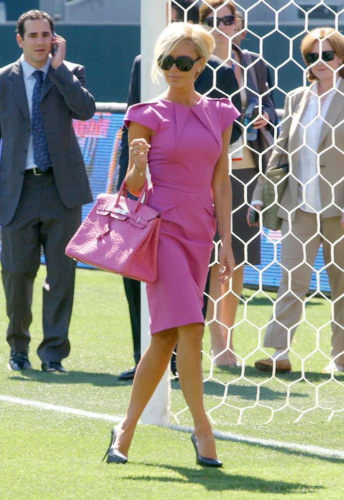 Victoria Beckham attending a soccer match in a fuchsia-pink dress, six-inch heels, and a crocodile-skin Hermès  Birkin bag.