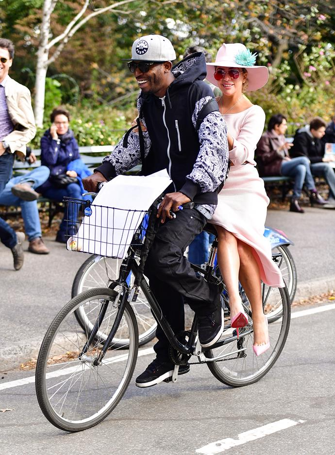 Lady Gaga riding a bike in a baby pink dress and Louboutin heels.