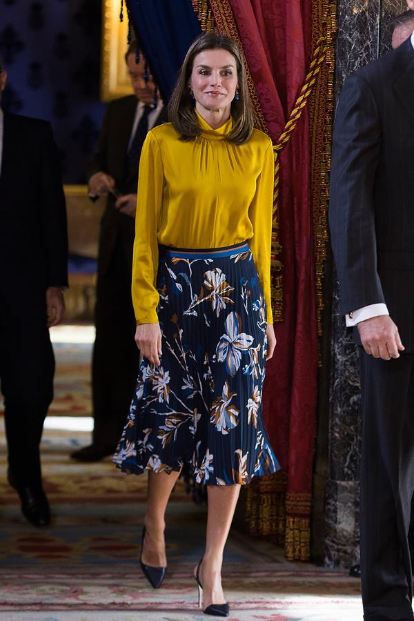 Receiving Palestinian President Mahmoud Abbas at the Royal Palace in Madrid wearing a mustard satin blouse and pleated floral midi skirt.