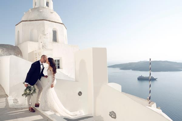 **On the location:  **   This was the most important and stressful part of the whole planning. We were limited with venues because of our large guest list. We also we wanted it to be quite traditional, outdoors and have the magical Santorini views.  We held the ceremony and reception on the rooftop of a private villa called Cavo Ventus in Santorini Greece.    The villa is located in a town called Akrotiri, nine kilometres away from the main town, Thira. The villa is built around the old stone windmill that is 200 years old and is perched on the edge of the caldera overlooking the volcano and sunset. It is absolutely amazing.