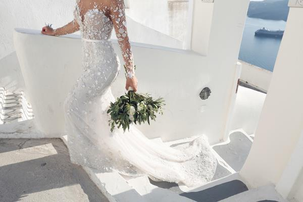**On the flowers: **   Santorini speaks for itself and we didn't want to take away from the natural surroundings so we kept our flowers quite simple. We used floral arrangement for our table centre piece and ceremony arch, which included olive tree branches and white roses. My bouquet also had olive tree branches with white peonies and our flower girl, Jemma, wore a floral crown that had olive tree branches with white roses.