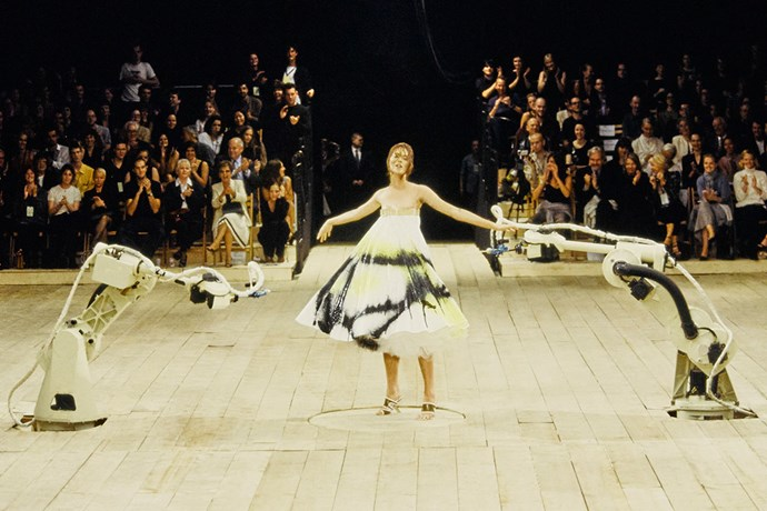 **ALEXANDER MCQUEEN SPRING 1999** <br><br> Alexander McQueen's spring 1999 show is arguably one of the most iconic fashion show finale's of all time. The show ended with model Shalom Harlow on a rotating platform, in a strapless dress that was cinched across the bust with a leather belt. Robots, which were typically used to paint cars, then shot paint at her dress, which resulted in the finished design. It was a complete work of art.