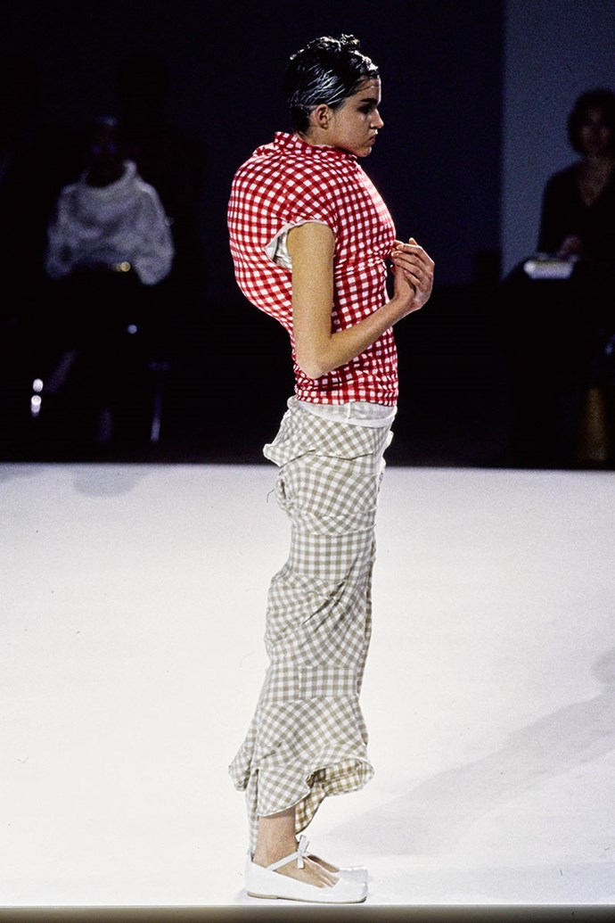 """**COMME DES GARÇONS SPRING 1997** <BR><BR> Rei Kawakubo has never been afraid to be different, and in her spring 1997 collection titled 'Body Meets Dress, Dress Meets Body', she did just that. The show, which was often referred to as """"lumps and bumps"""", featured tube gingham dresses that were stuffed with lumpen filler. Some said her creations were deformed, however, she insisted on taking risks and creating new silhouettes."""