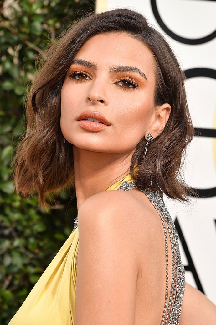 **EMILY RATAJKOWSKI** <br><br> Model of the moment, Emily Ratajkowski, attended her first Golden Globe Awards red carpet in 2017. Her subtle beachy waves were complemented with yellow and orange eyeshadow—her makeup matched her stunning gown, of course.