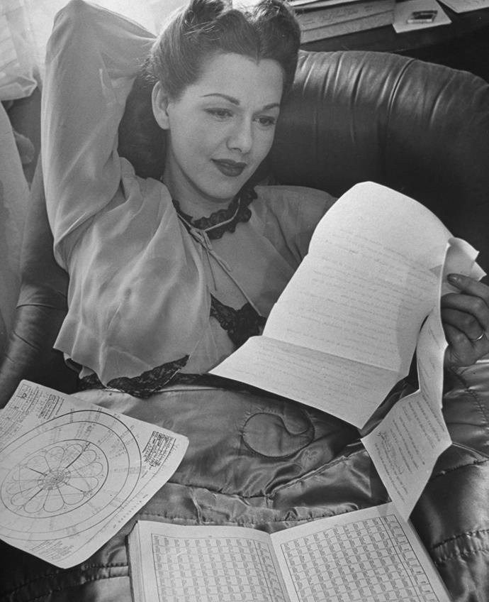 Actress Maria Montez reading her horoscope, 1946.