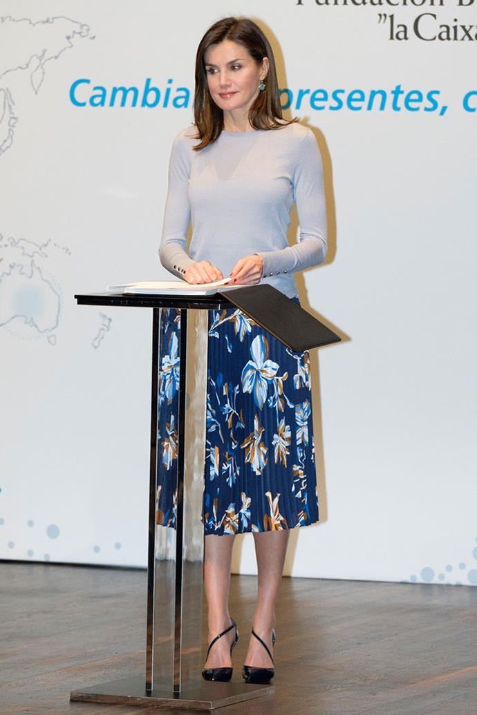 Queen Letizia presents the 26th Caixa Scholarship award on April 10, 2018 in a classic sky blue top paired with a pleated floral Hugo Boss skirt.
