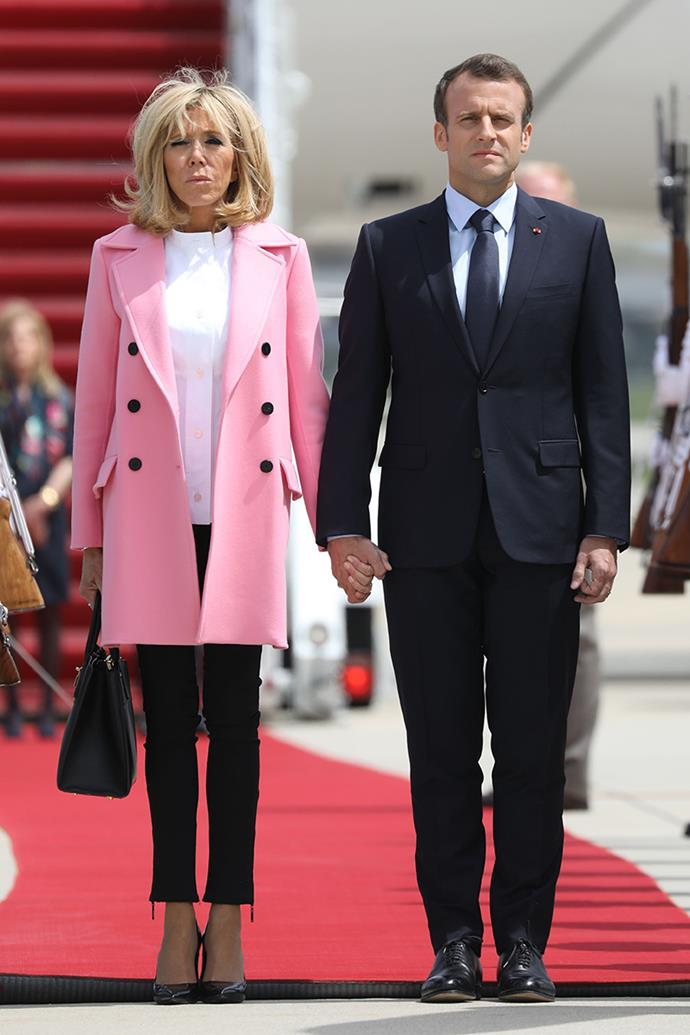 Brigitte Macron lands in the United States, alongside her husband Emmanuel Macron, wearing a sorbet pink coat by Louis Vuitton, teamed with the French house's famous Steamer Bag.