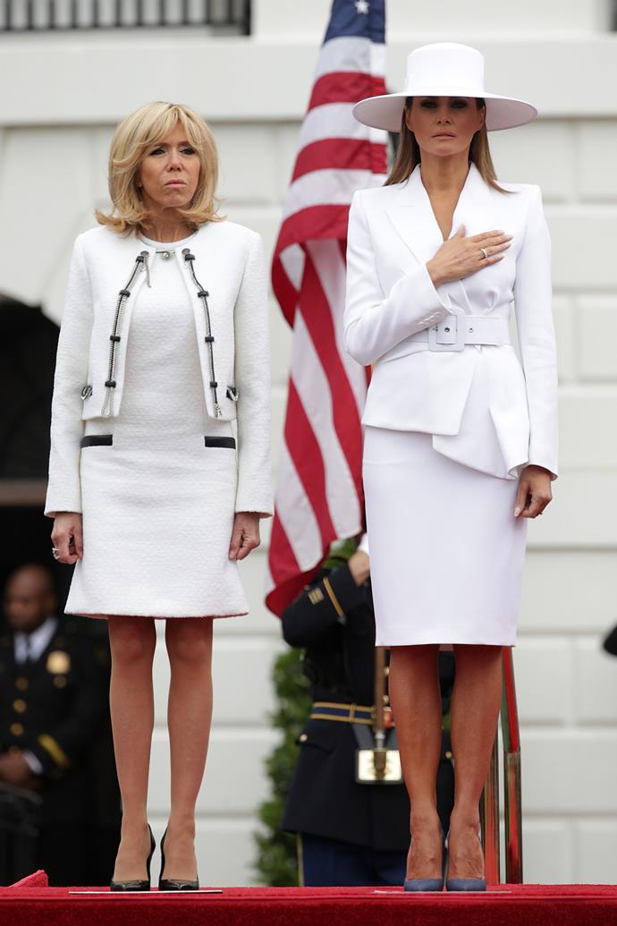"Melania Trump and French First Lady Brigitte Macron on the white lawn of The White House. Melania wears a white suit by Michael Kors. The look is already being [mercilessly turned into memes](https://www.nytimes.com/2018/04/24/style/melania-trump-white-hat.html|target=""_blank""