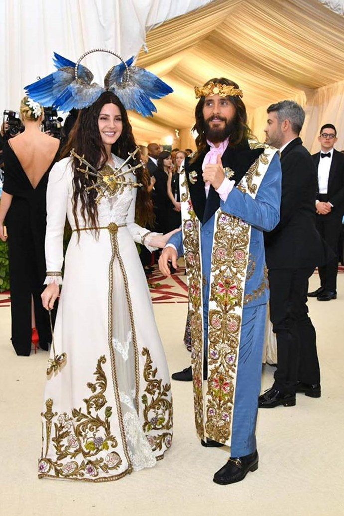"""**Lana Del Rey in Gucci and Jared Leto in Gucci**<br><br>  """"Loving the sense of humour injection here. Also full points to Alessandro Michele for casting Jared Leto as handsome Jesus."""" - Clare Maclean, fashion features director<br><br>  """"When I heard Lana was wearing Gucci, I knew it would be a match made in heaven. Gucci's maximalist, OTT style really lends itself to this theme, and the attention to detail in Lana's Mother Mary look is incredible. From her 'Seven Sorrows' pierced heart, her halo, and her 'Eyes of St Lucia' scepter, everything worked."""" - Mahalia Chang, digital features editor <br><br> """"The """"Gucci family"""" looked so incredible. Perfect amount of fashion and fun. Daggers in the heart are next level."""" - Caroline Tran, junior fashion editor<br><br>  """"Lana Del Rey went all-out for this year's red carpet and her bravery needs to be commended. Sure, the sword-heart detailing and feathered halo are beyond extravagant, but it's the Met Gala, so this OTT costume-inspired approach to fashion works perfectly."""" - Natasha Harding, digital fashion writer"""