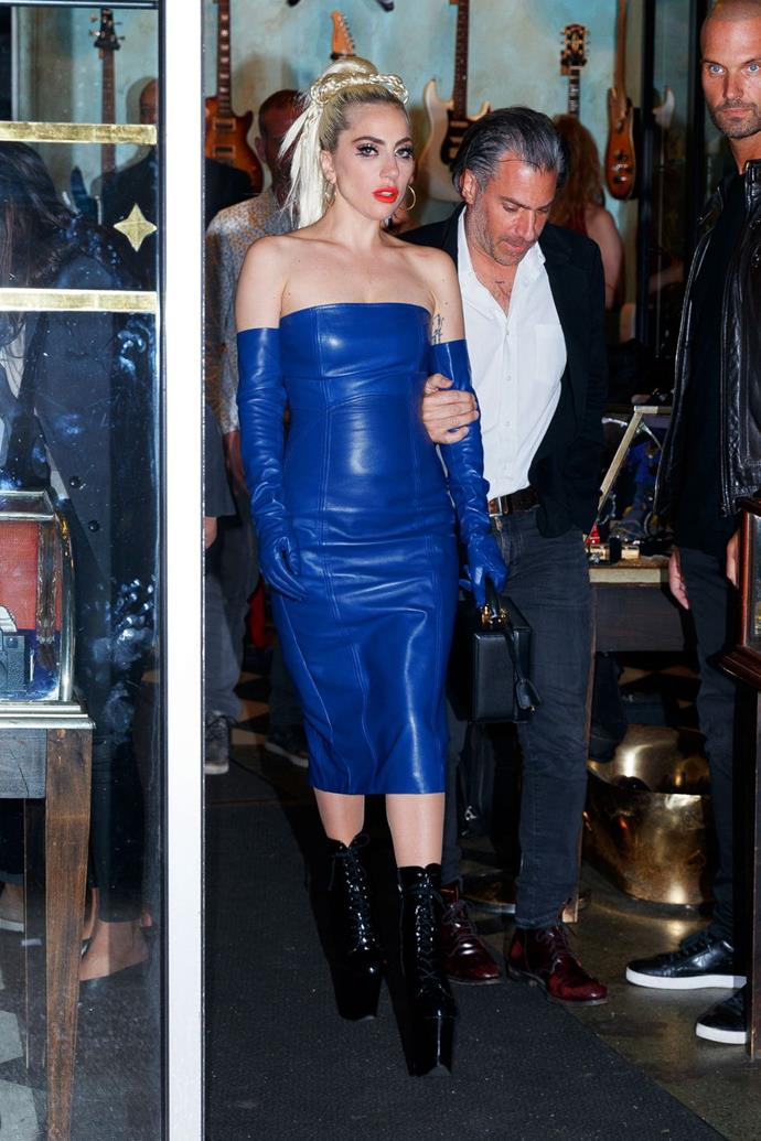 May 28:   <br><br> Once again rocking her hair bow, Gaga tapped into her Fame Monster days by wearing a blue leather dress, matching gloves, and sky-high patent heel platform boots.