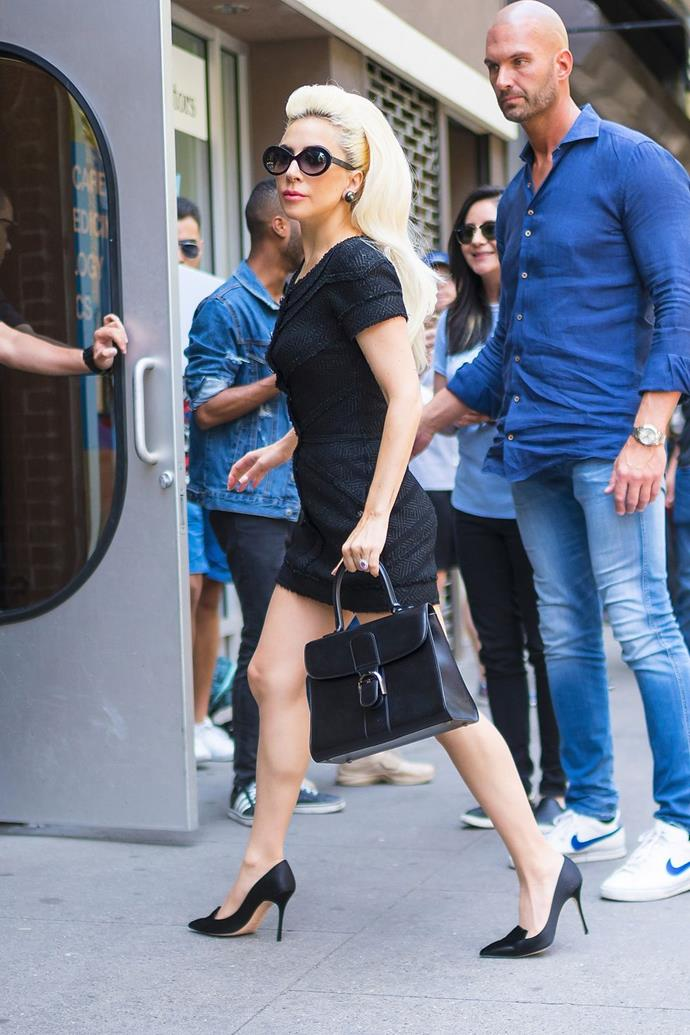 """**May 25:**   <br><br> On Friday, the singer hit the studio once again in a polished little black dress, oversized sunnies, a Delvaux bag, and pumps for a look that practically screamed """"I'm about to sue you for every penny you have."""""""