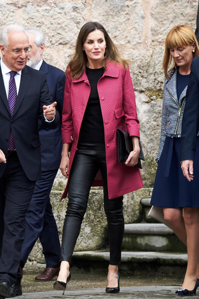Queen Letizia of Spain just stepped out at the 13th International Seminar of Language and Journalism wearing a blush overcoat and a pair of fitted black leather trousers. The rock n' roll worthy pants are so far from the conservative princess fashion brief prescribed for British royals, chances are we'd never see the Duchess of Cambridge, Kate Middleton, or the Duchess of Sussex, Meghan Markle, wearing them.
