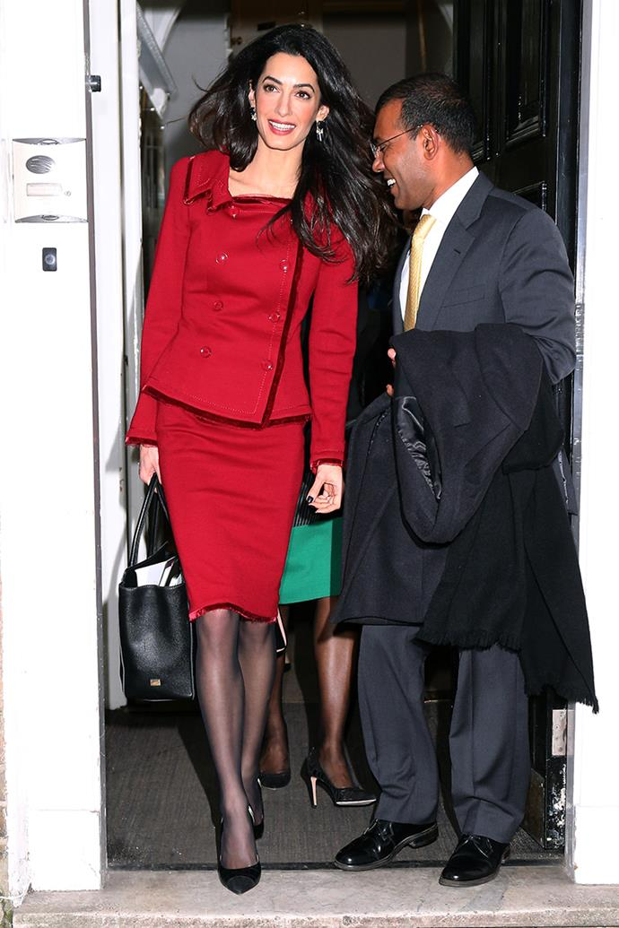 Wearing a scarlet red skirt suit and tights in London on January 25, 2016