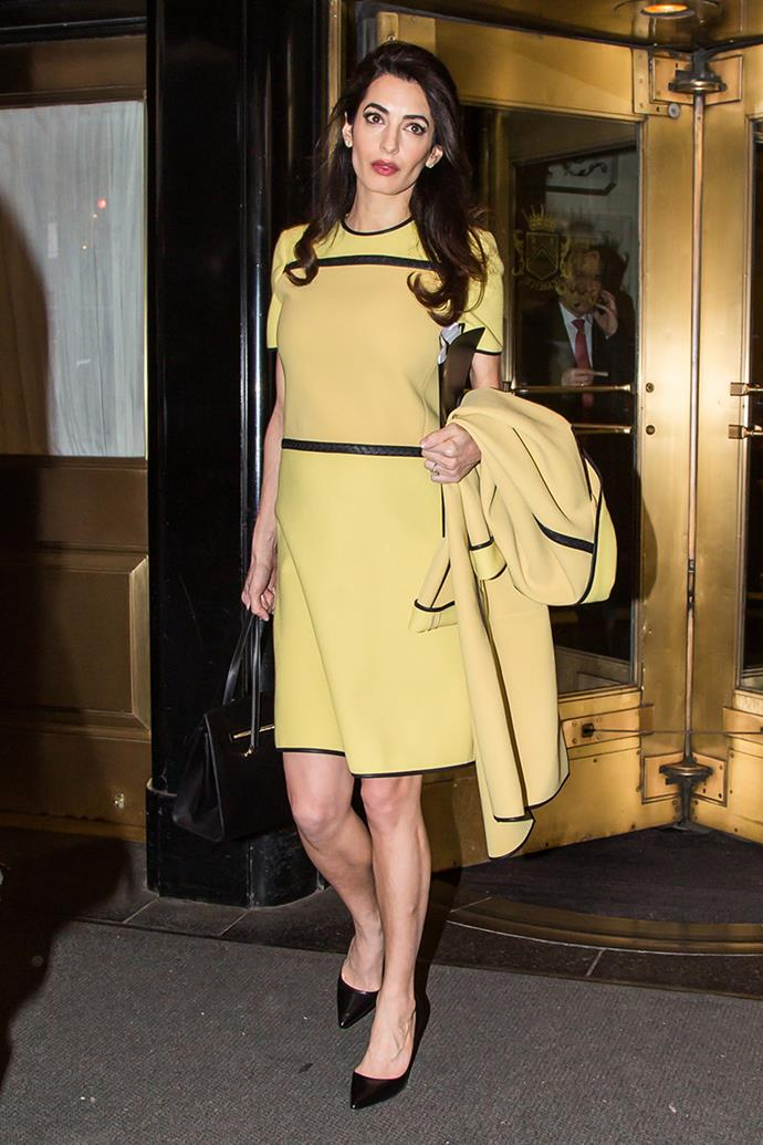 Wearing a pastel yellow dress with black panel detailing in New York City on March 9, 2017