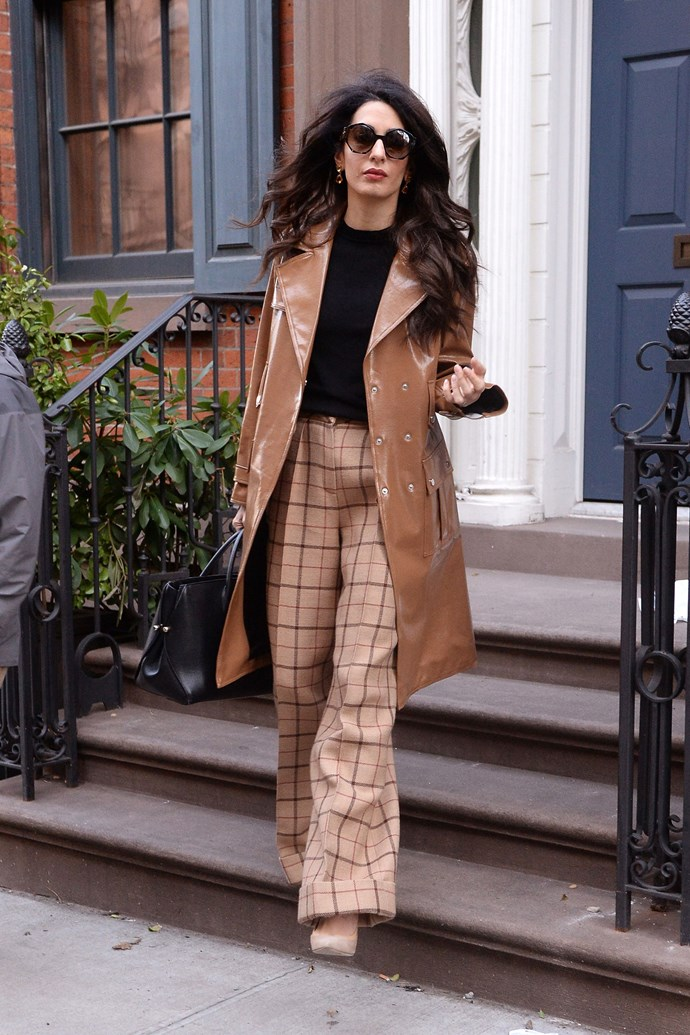 Wearing a caramel Diane Von Furstenberg patent leather trench, check trousers and a Dior bag in New York City on April 8, 2018 <br><br>  Image: Splash