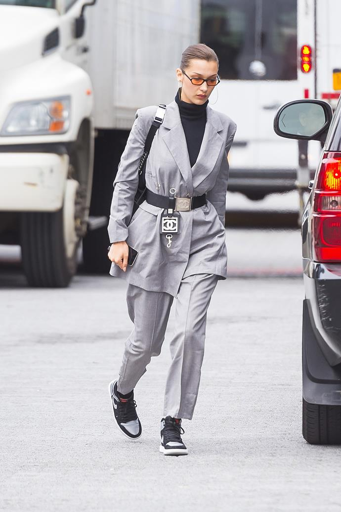 In New York, wearing a slouchy grey suit, turtle neck, Nike sneakers and a vintage Chanel belt.