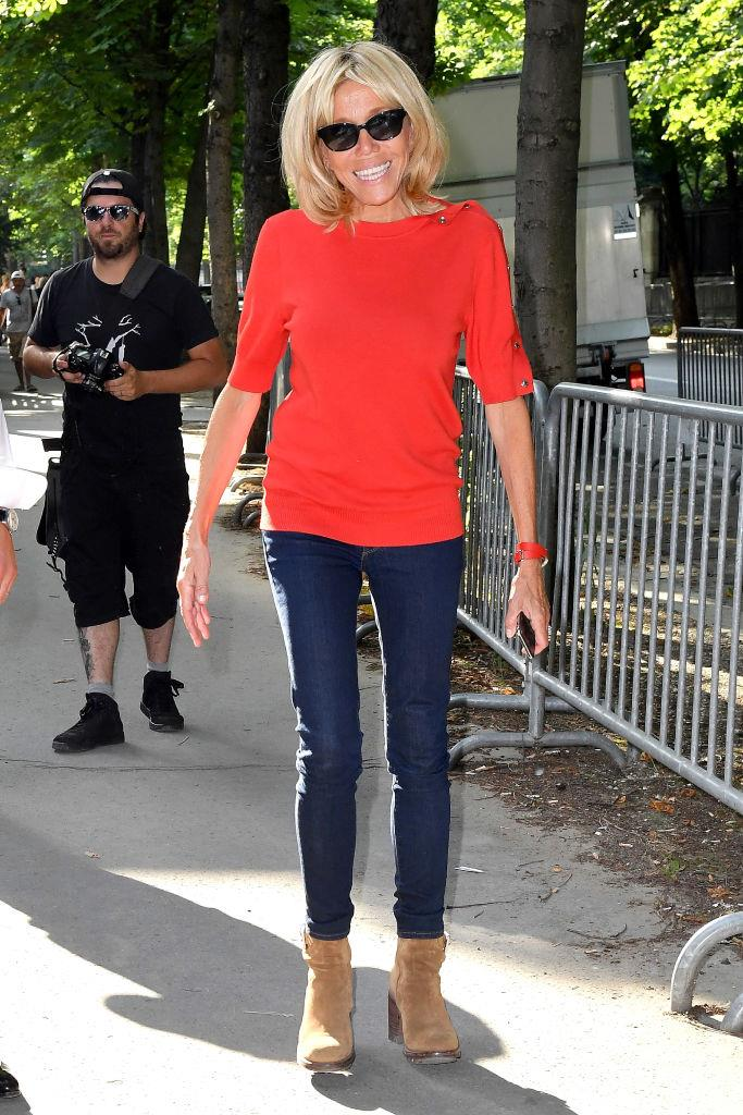 Brigitte Macron opted for a surprisingly understated look today while attending the Giambattista Valli Show at Couture Fashion Week in Paris. The First Lady kept her casual look sleek by pairing a burnt orange top with a pair of indigo denim jeans.