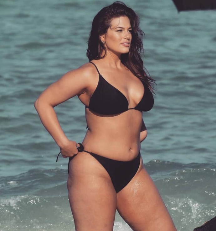 Ashley Graham adjusts her bikini on the beach.