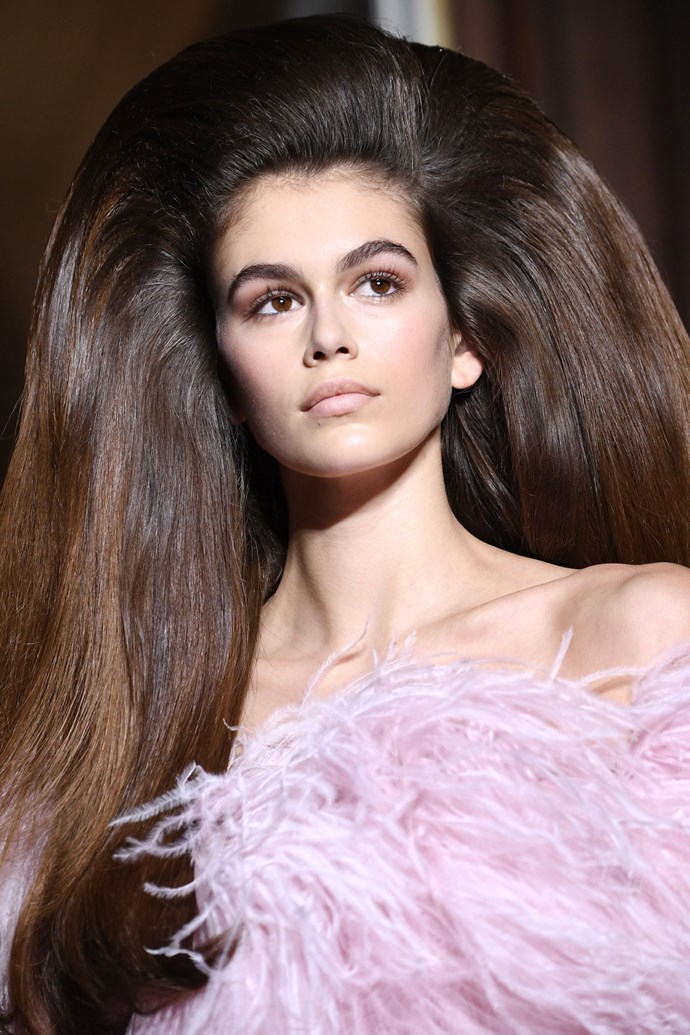 "**VALENTINO HAUTE COUTURE: '60S PRISCILLA PRESLEY** <br><br> When we first saw Kaia Gerber walking down the Valentino runway in that huge backcombed wig, the first thought that came to mind was Priscilla Presley's hair look when she wed Elvis. Despite the extreme heights it reached, the hair look for Valentino still maintained a chic and feminine look, pairing perfectly with the billowy gowns they wore. <br><br> But getting the model's hair to reach epic proportions was no mean feat. Lead stylist for the show, Josh Wood, shared on [Instagram](https://www.instagram.com/p/Bk0puQWhg1q/|target=""_blank""