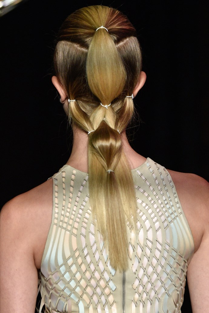 **IRIS VAN HERPEN HAUTE COUTURE: WOVEN PONYTAILS** <br><br> The incredibly detailed take on the ponytail on Iris Van Herpen has elevated the simple style to new levels. <br><br> Parting the model's hair into top and bottom sections, multiple ponytails were woven and intertwined with each other to create a super sculptural hair look that matched the highly-detailed and dimensional looks they wore on the runway.