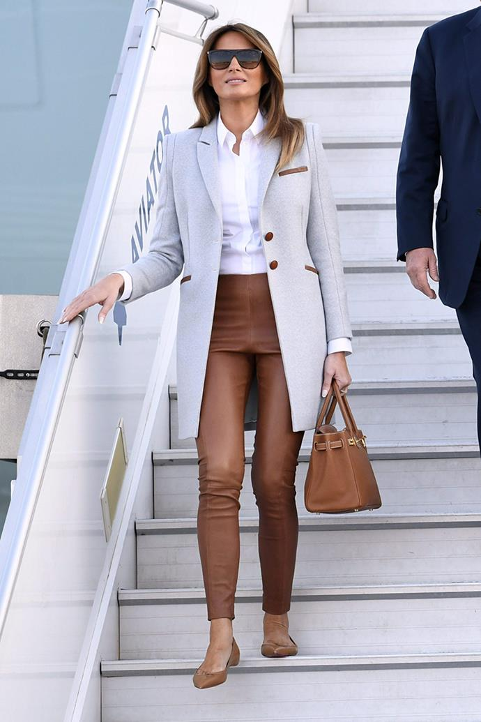 Melania Trump arrives at Helsinki airport wearing a tailored grey coat complete with brown leather detailing, tan leather trousers, an Hermès Birkin and matching flats.