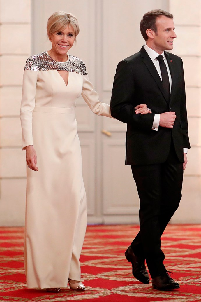 Arriving for a State dinner wearing a plunging ivory Louis Vuitton, finished with a sequin silver cape, at the Elysée Palace on 19 March, 2018.