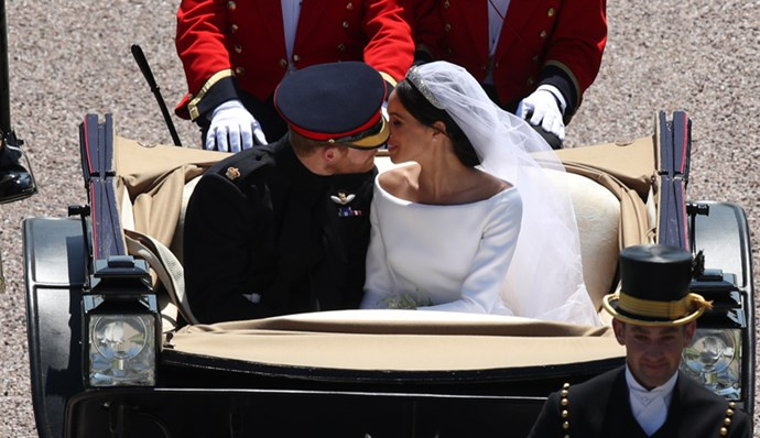Prince Harry and Meghan Markle kiss in the Ascot Landau Carriage as their carriage procession rides along the Long Walk after their wedding ceremony on 19 May, 2018.