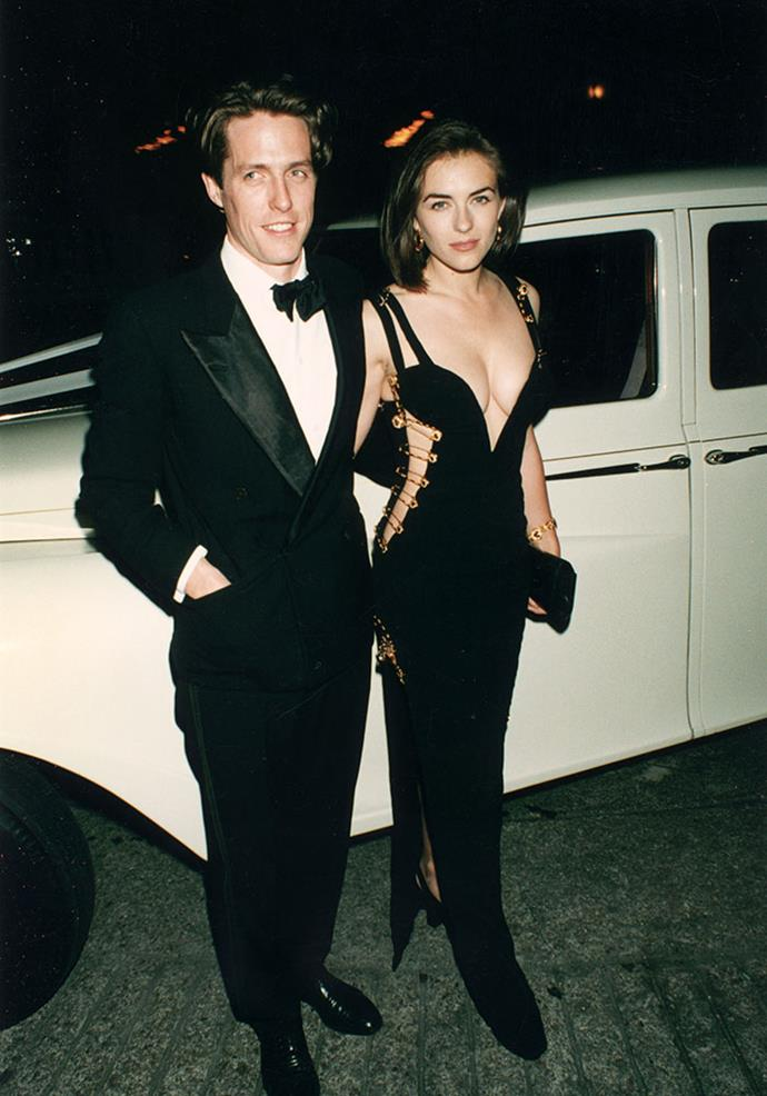 Elizabeth Hurley in a Versace dress with safety-pin detail (often referred to simply as '*That Dress*') with then-boyfriend Hugh Grant at the premiere of *Four Weddings and a Funeral*, 1994.