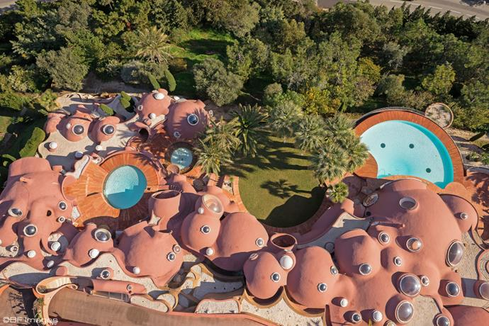 "An aerial view of the Bubble House, showcasing its iconic shape (and multiple swimming pools).  <br><br> *Image: [WWD](https://wwd.com/fashion-news/fashion-scoops/gallery/pierre-cardins-bubble-palace-for-sale-for-300-million-euros-10560136/#!4/a-view-of-pierre-cardins-bubble-palace-5|target=""_blank"")*"