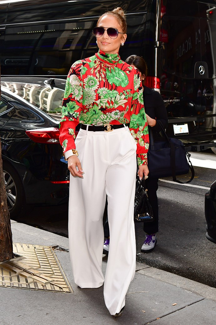 Jennifer Lopez steps out in New York City wearing a contrasting print floral blouse, with wide leg ivory trousers and a gold Chanel buckle belt on 2nd August, 2018.