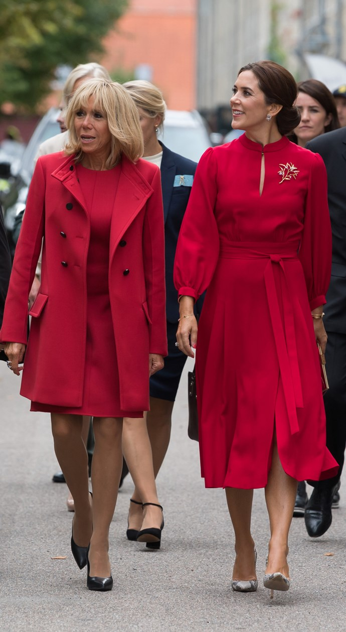 **August 2018** <br><br> French First Lady, Brigitte Macron, and Mary, Crown Princess of Denmark, both stepped out in Copenhagen wearing matching ruby red dresses. Macron wore a custom Louis Vuitton mini, that stopped just above the knees, which she than paired with a matching coat and black leather pumps. Mary opted for a mid-calf length dress, with billowing sleeve and keyhole neck detailing, which she then accessorised with a floral brooch and a pair of python pumps.
