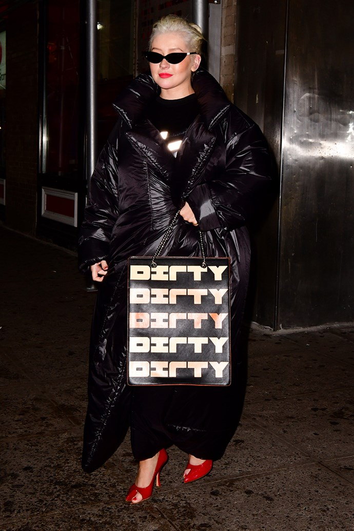 Christina Aguilera just stepped out at New York Fashion Week wearing a puffy Norma Kamali coat dress, scarlet red Y/Project pumps and a custom House Of Holland bag emblazoned with the name of her 2002 hit single, 'Dirrty'.